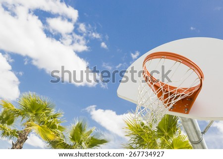 Abstract of Community Basketball Hoop and Net and Palm Trees Against Blue Sky. - stock photo
