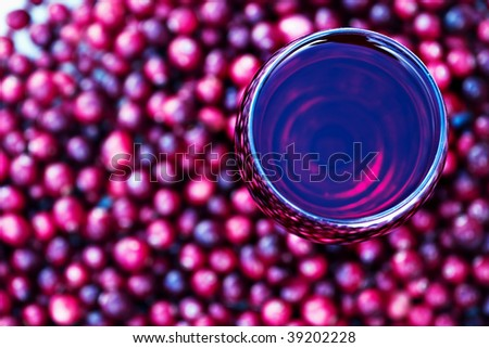 Abstract of cranberry juice with fresh cranberries. Shallow DOF with focus on glass of juice. - stock photo