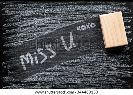 Abstract of Duster and chalk in front of blackboard. text miss you on black board. - stock photo