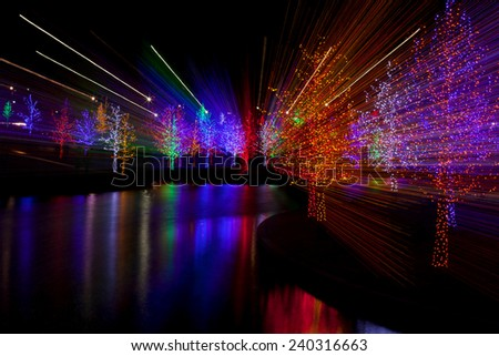 Abstract of trees tightly wrapped in LED lights for the Christmas holidays reflecting in lake. Each tree is wrapped in one color. Camera zoom use to produce light streaks on long exposure - stock photo