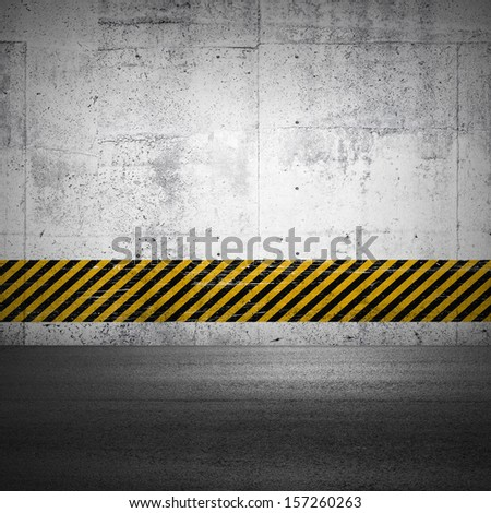 Abstract parking interior fragment with asphalt ground and striped yellow and black pattern on the concrete wall   - stock photo