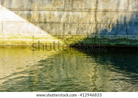 Abstract pattern from under a bridge. Natural sunlight coming in from the left is reflected in the water and results in four different light zones, all converging in the center. - stock photo