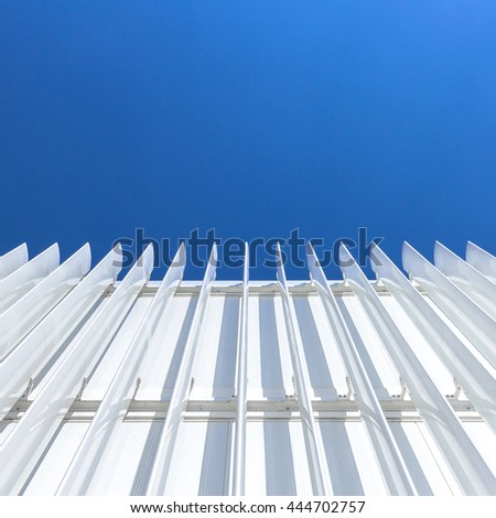 Abstract perspective of the facade of a modern building covered with white panels - stock photo