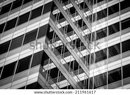 abstract photo of a modern glass building with crossing lines and reflections - stock photo