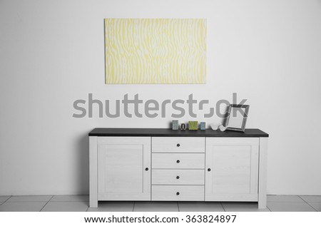Abstract picture with commode, frame and inscription home on a white wall background - stock photo