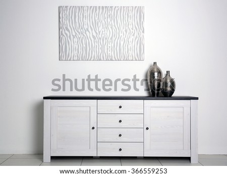 Abstract picture with vases and commode on a white wall background - stock photo