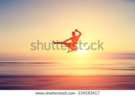 abstract piece of art. man performing flying kick on a blurred surface that looks like a beach at sunset - stock photo