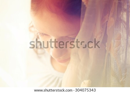 abstract portrait of thoughtful little girl near window. retro filtered image - stock photo