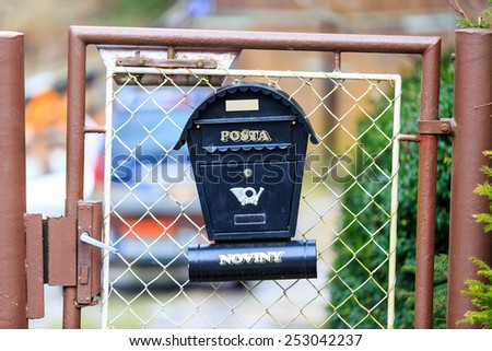 Abstract post box on gate - stock photo