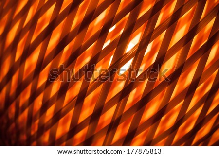 Abstract red background with macro of wicker lampshade - stock photo