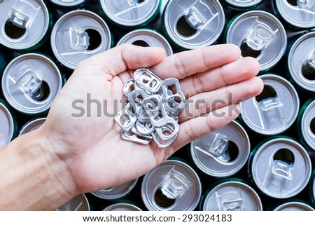 Abstract ring pull aluminum of cans on hand with many cans background - stock photo