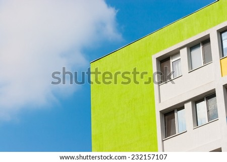 Abstract scene of a green apartment building in angle against blue sky and white clouds. - stock photo