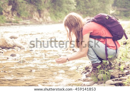 abstract shot of girl hiker drinking a water from the river against a bright sunlight - stock photo