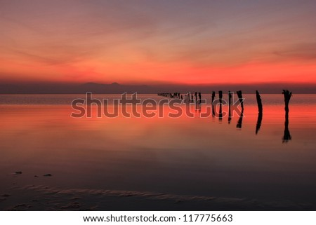 Abstract sunset reflection with old fence posts, Great Salt Lake, Utah, USA. - stock photo