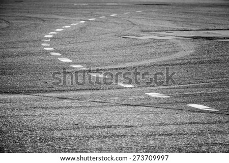 Abstract transportation background. White bent lines over dark rough asphalt, road marking. Selective focus with shallow DOF - stock photo