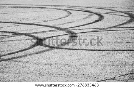 Abstract transportation background with dark tire tracks on gray asphalt road, selective focus with shallow DOF  - stock photo