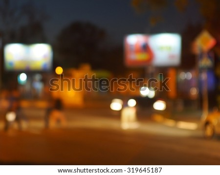 Abstract urban night scene with blurred headlights on the road. Blur and defocused lights from the headlights of cars and traffic lights can be used as background. - stock photo