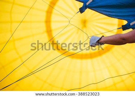 Abstract view inside a yellow hot air balloon and the pilot hand - stock photo
