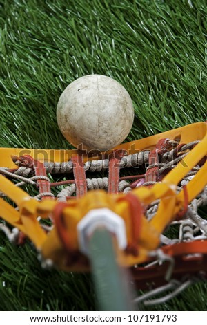 Abstract view of a lacrosse stick scooping up a ball on a green turf field. - stock photo