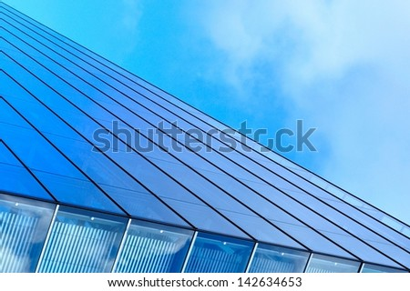 Abstract view of modern blue glass business center on a clear sky background - stock photo