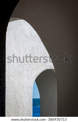 Abstract view of the sea through the arches of a Greek hotel. Images from the Greek Islands of Skopelos and Skiathos, popular tourist destinations in the Mediterranean. - stock photo