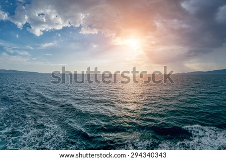 Abstract Warm Sunset at Sea with Waves, Clouds and Foam - stock photo