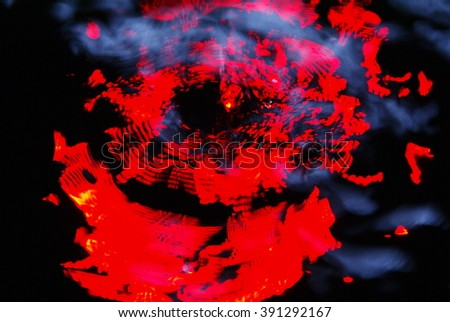 Abstract water like background. Red lights reflected on the water. Water splash on black background. Intentional motion blur. - stock photo