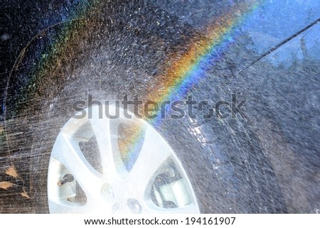 abstract water splash with rainbow during washing car wheel  - stock photo