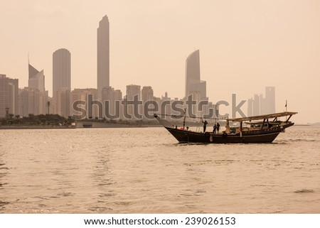 Abu Dhabi buildings skyline with old fishing boat on the front. - stock photo