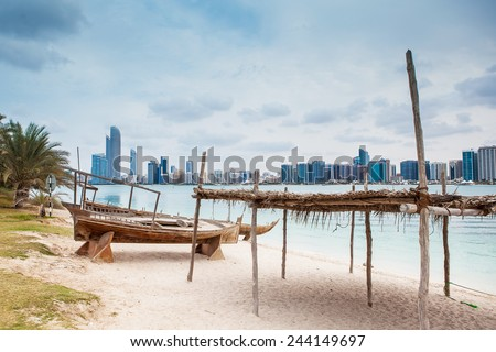 abu dhabi sea beach with old wooden boath and luxury skyscarper - stock photo