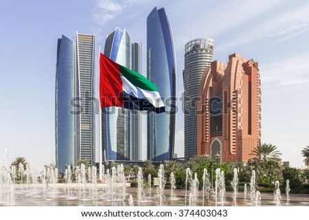 ABU DHABI, UAE - OCTOBER 23, 2015: Etihad tower ensemble in Abu Dhabi with fountains and flag in the foreground - stock photo