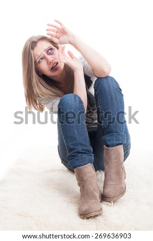 Abused and injured woman acting scared by protecting herself from an imaginary husband, man, or boyfriend - stock photo