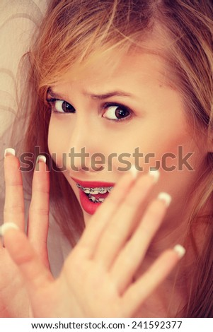 Abused young woman trying to hide and defend herself - stock photo