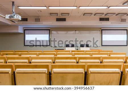 Academic auditorium with wood chairs, projector and board - stock photo
