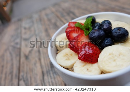 acai berry bowls with fresh fruit  strawberry, blueberry, banana and peppermint leaves in white cup on the wooden table. good smoothie dessert for summer. - stock photo