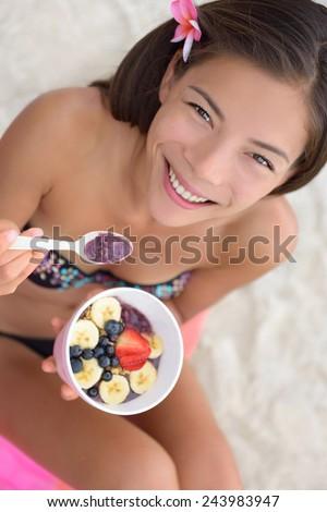 Acai bowl - woman eating healthy food on beach. Girl enjoy acai bowls made from acai berries and fruits outdoors on beach for breakfast. Girl on Hawaii eating local Hawaiian dish. - stock photo