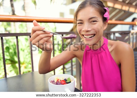 Acai bowl - woman eating healthy food smiling happy. Girl enjoy acai bowls made from acai berries and fruits outdoors for breakfast. Girl on Hawaii eating local Hawaiian dish. - stock photo