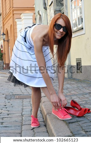 Acallosity.  The beautiful woman changes the shoes. - stock photo
