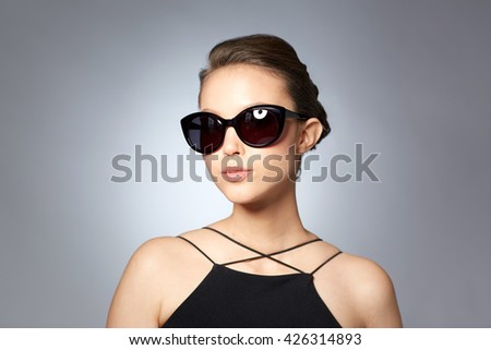 accessories, eyewear, fashion, people and luxury concept - beautiful young woman in elegant black sunglasses over gray background - stock photo