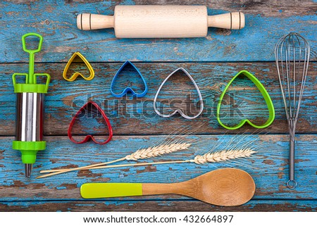 Accessories for baking. Cookie cutters, pastry syringe, whisk on a wooden background. - stock photo