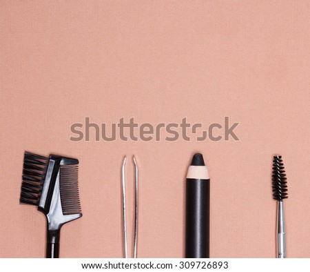 Accessories for care of brows: eyebrow pencil, tweezers, brush and comb on peach colored textured surface. Eyebrow grooming tools. Copy space in the upper portion of the image - stock photo