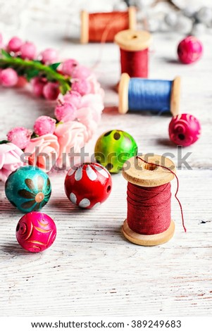 Accessories for jewelry.Round colored beads,spools of threads for needlework - stock photo