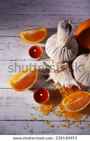 Accessories for massage therapy with candle light on color wooden background - stock photo
