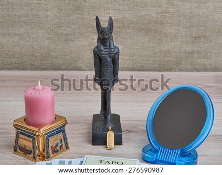 Accessories for predictions  -  tarot cards, cartouche,  Anubis's figurine, candle in  Egyptian candlestick, mirror - lie on a table  - stock photo