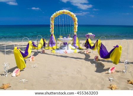 Accessory kit for a wedding is on the shores of the Caribbean Sea. Arch is decorated with curtains and flowers. - stock photo