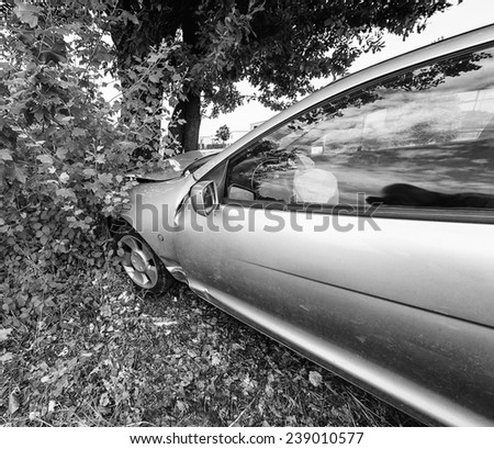 Accident car crash on an city road against a tree. - stock photo