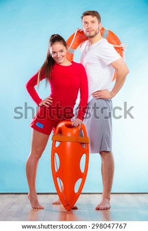 Accident prevention and water rescue. Full length man and woman lifeguard couple holding buoy lifesaver equipment on blue - stock photo