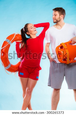 Accident prevention and water rescue. lifeguard couple on duty woman leaning on man arm, holding buoy lifesaver equipment on blue - stock photo