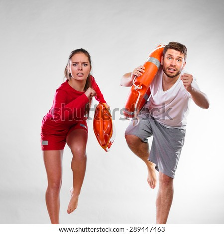 Accident prevention and water rescue. man and woman lifeguard couple on duty running with with life belt lifesaver equipment on gray - stock photo