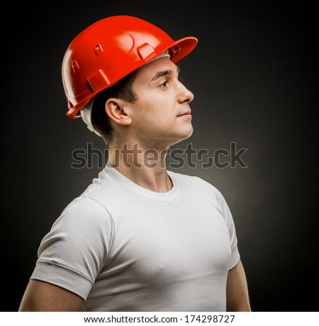 Accident prevention - safety helmet. White man in a protective helmet construction in the studio on a black background in profile - stock photo